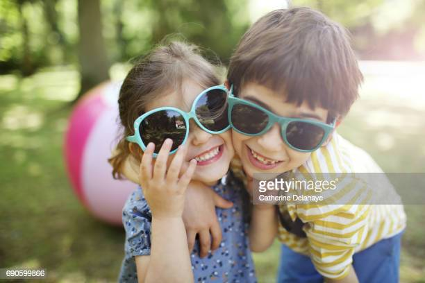 A brother and a sister, wearing sun glasses, posing together