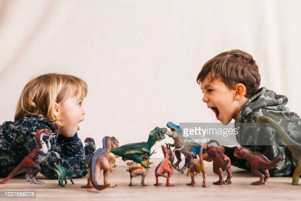 brother and his little sister playing with toy dinosaurs - broer stockfoto's en -beelden