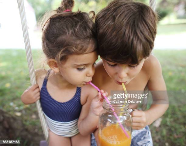 A brother and his sister drinking orange juice seating on a swing