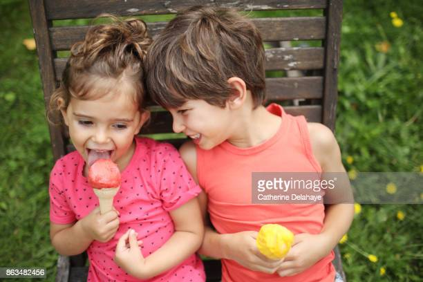a brother and his sister eating icecream in the garden - nur kinder stock-fotos und bilder