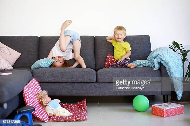 A brother and his sister playing on a sofa