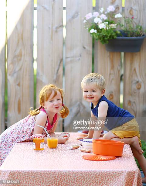A brother and his sister taking their breakfast