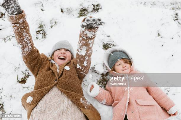 brother and little sister lying side by side on snow-covered meadow - froid humour photos et images de collection