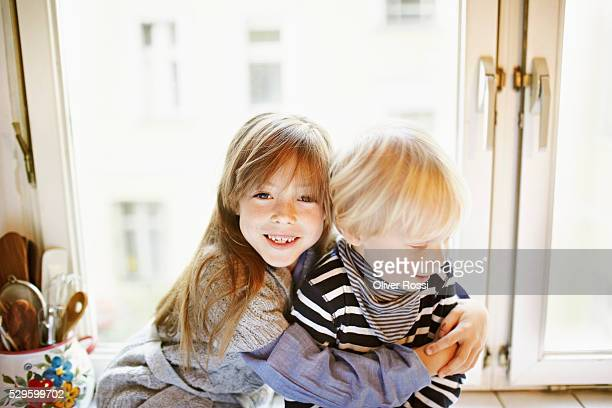 Brother and sister [2-5] hugging