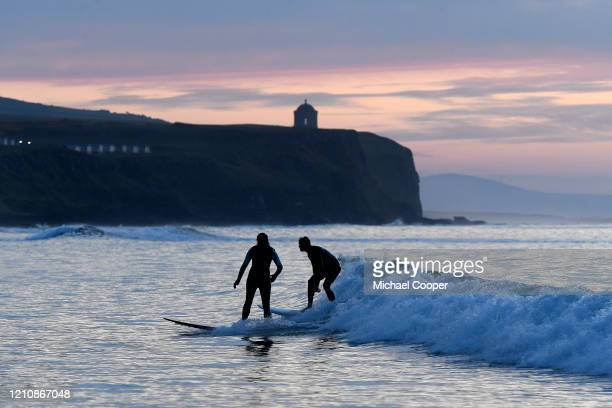 Brother and sister, Aran and Lindsey Lyons enjoy a sunset surf alone last night under Mussenden Temple on Castlerock beach, County Londonderry, on...