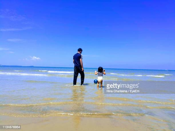 Brother And Sister At Beach Against Blue Sky