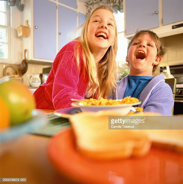 brother and sister (8-11) at breakfast table laughing - solo bambini foto e immagini stock