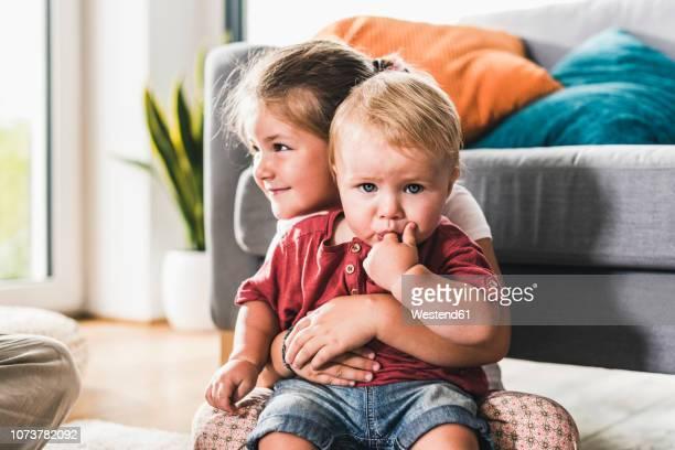 brother and sister at home in living room - sorella foto e immagini stock