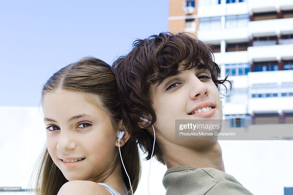 Brother and sister back to back, listening to earphones, smiling at camera : Stock Photo