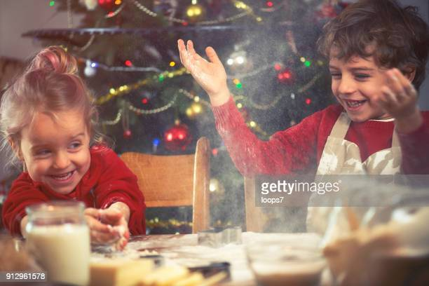 brother and sister baking cookies - teasing stock pictures, royalty-free photos & images