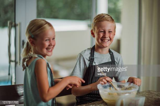 brother and sister baking fun in the kitchen during lockdown looking away - zakelijke kleding stock pictures, royalty-free photos & images