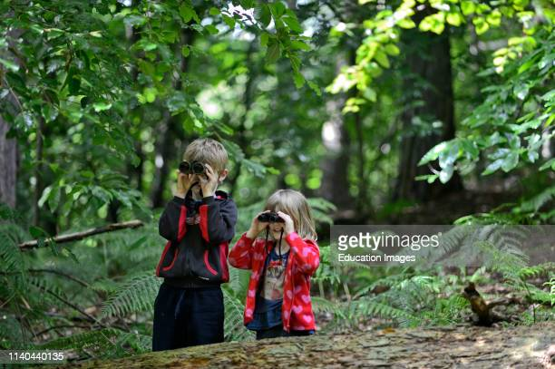 Brother and sister bird watching in woodland in summer Norfolk