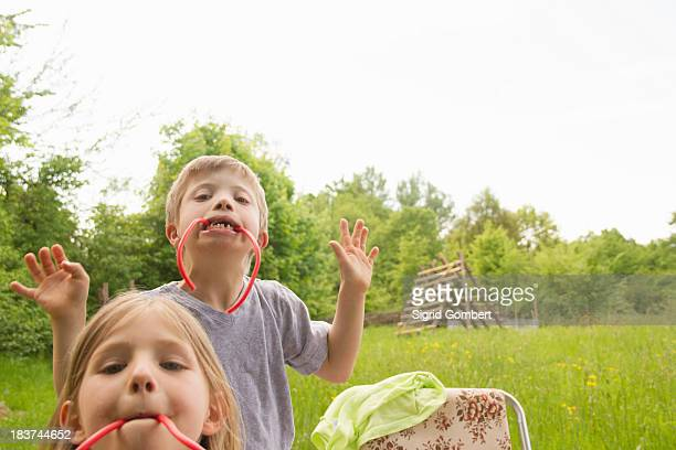 brother and sister biting on liquorice - sigrid gombert stock pictures, royalty-free photos & images