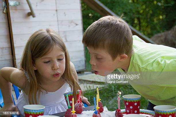 brother and sister blowing out birthday candles - sigrid gombert stock-fotos und bilder