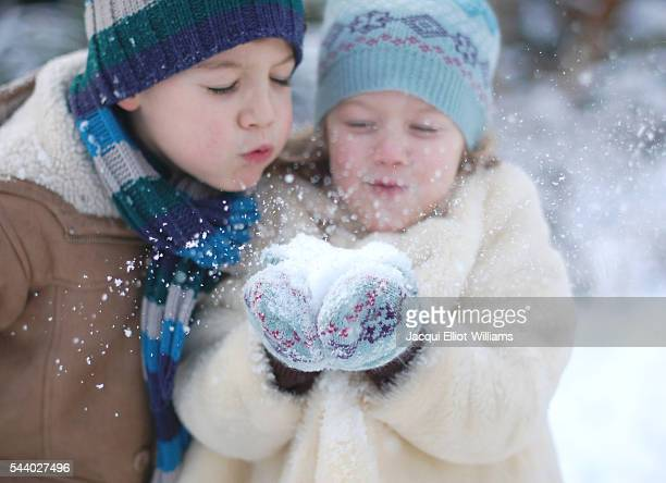 A brother and sister blowing snow towards the camera.