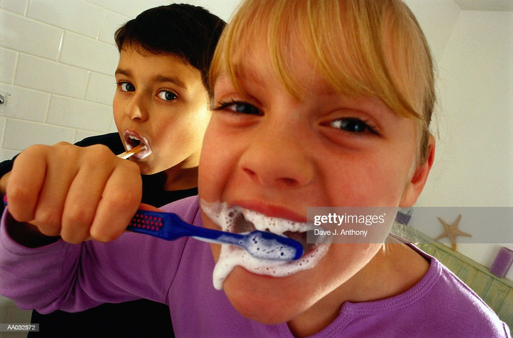 Brother and Sister Brushing Their Teeth : Stock Photo