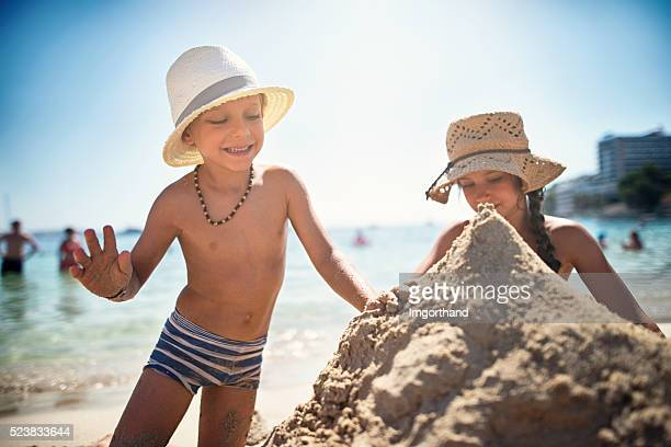 Brother and sister building a sandcastle on the beach