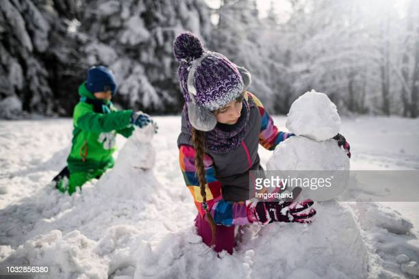brother and sister building snowmen in winter forest - snowman stock pictures, royalty-free photos & images
