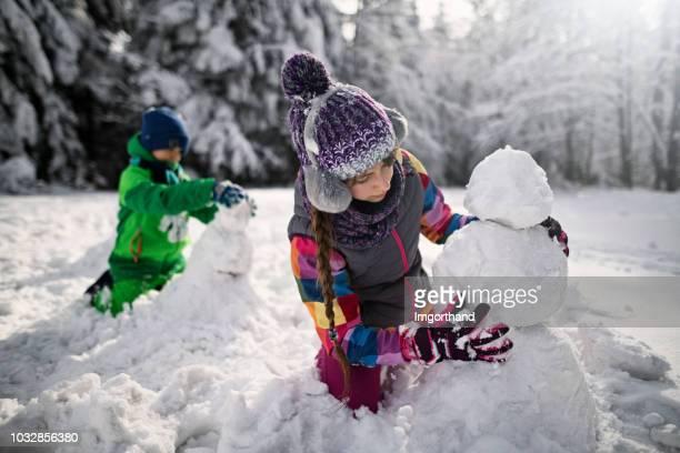 frère et sœur, construire des bonhommes de neige dans la forêt d'hiver - bonhomme de neige photos et images de collection