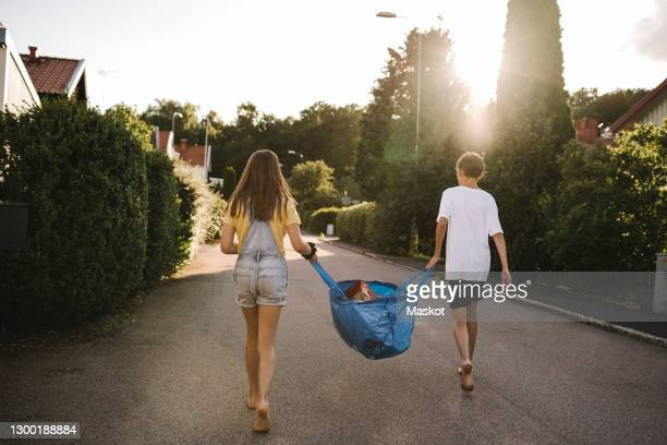 brother and sister carrying bag on road - chores stock pictures, royalty-free photos & images