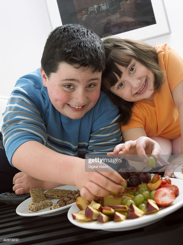 Brother and Sister Choosing Grapes from a Plate of Fruit : Stock Photo