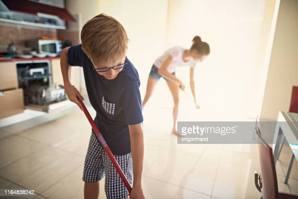 brother and sister cleaning kitchen - sweeping stock pictures, royalty-free photos & images