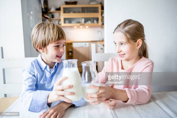Brother and sister clinking milk glasses