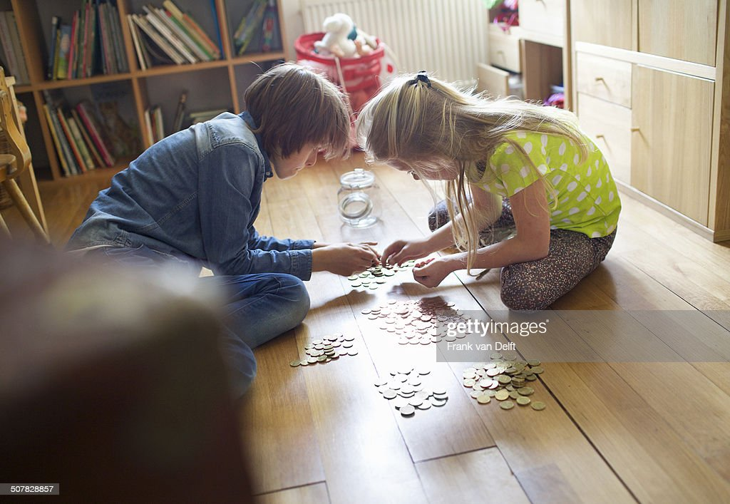 Brother and sister counting coins from savings jar : Stock Photo