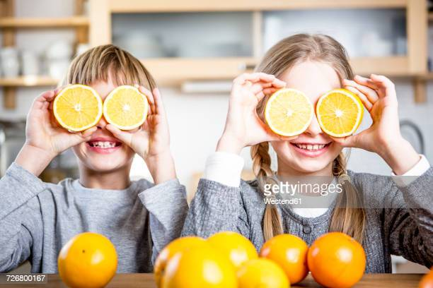 Brother and sister covering their eyes with slices of oranges