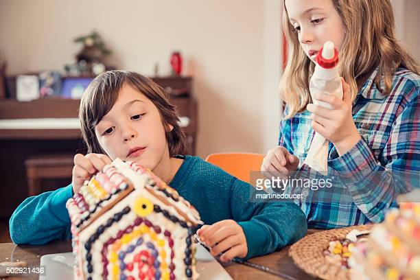 Brother and sister decorating gingerbread house at home.