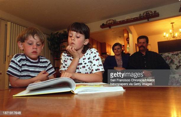 Brother and sister Douglas and Katie read from a book at their family home in San Bruno as Holly and Steve Paganelli look on in the background....