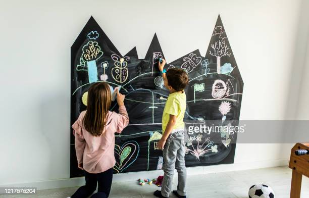 brother and sister drawing on the blackboard stock photo - chalk wall stock pictures, royalty-free photos & images