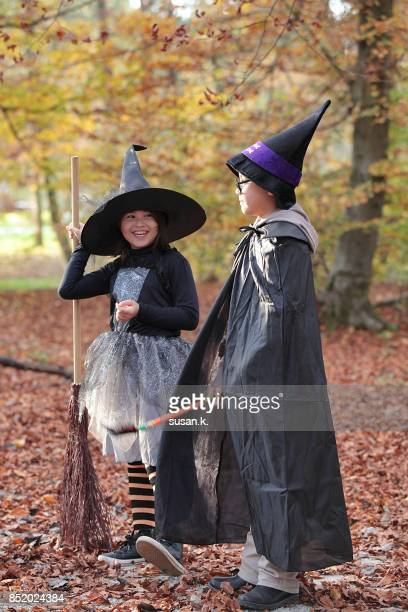 Brother and sister dressed up as wizard and witch, having fun in the forest.
