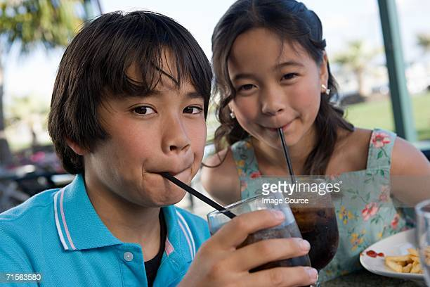 Brother and sister drinking cola