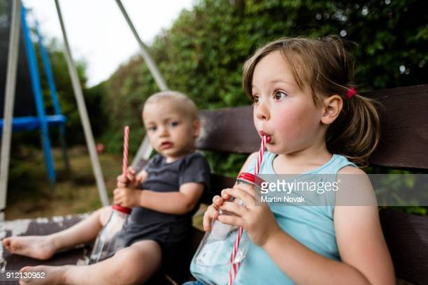 Brother and sister drinking water while sitting on bench