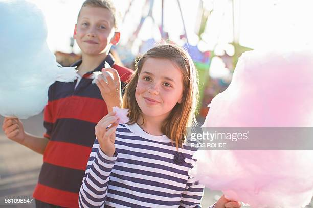 Brother and sister eating pink candyfloss at fairground
