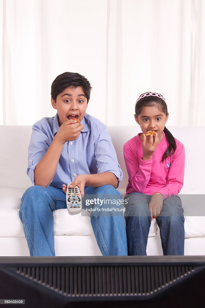 Brother and sister eating while watching tv : Stock Photo