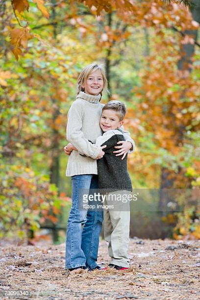 brother and sister embracing in woodland - brown jeans stock photos and pictures