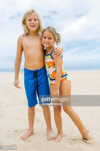 Brother (8-9) and sister (6-7) embracing on beach
