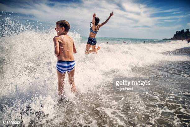 brother and sister enjoying huge waves on beach - imgorthand stock photos and pictures