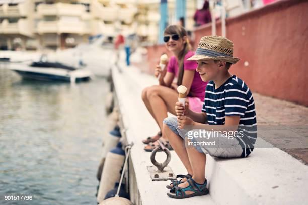 brother and sister enjoying ice cream sitting at benalmadena marina - marina stock photos and pictures