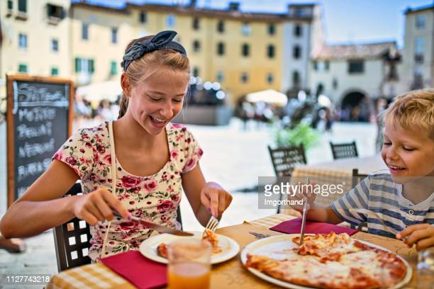 Brother and sister enjoying pizza lunch in Lucca street restaurant