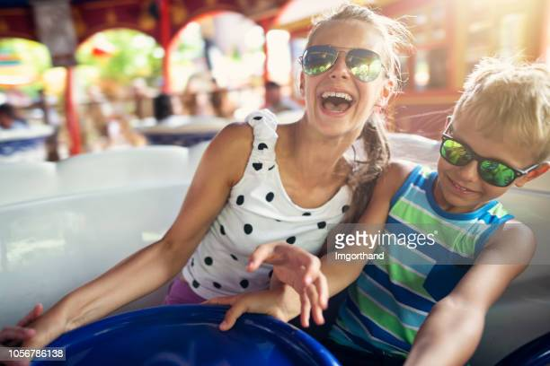 brother and sister enjoying spinning carousel - traveling carnival stock pictures, royalty-free photos & images