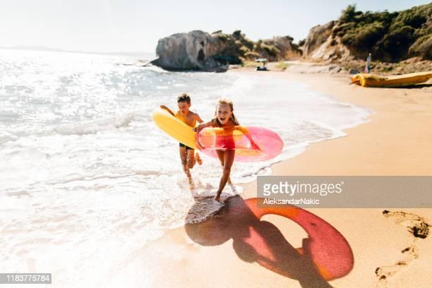 frère et soeur appréciant le matin d'été à la plage - vacances photos et images de collection