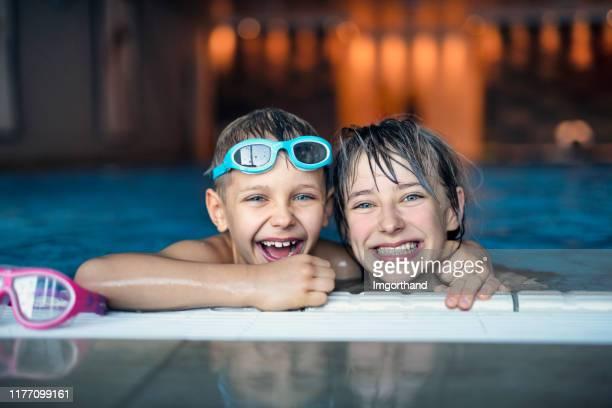 屋内スイミングプールで泳ぐ兄弟姉妹 - 室内プール ストックフォトと画像