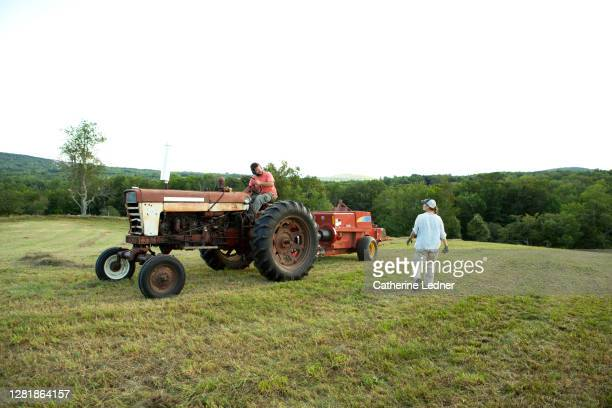 brother and sister farm owners with old tractor in empty hay field - catherine ledner stock pictures, royalty-free photos & images
