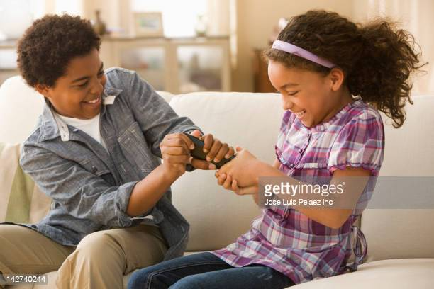 brother and sister fighting over remote control - brother stock pictures, royalty-free photos & images