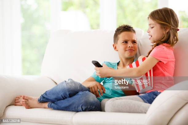 Brother and sister fighting over remote control