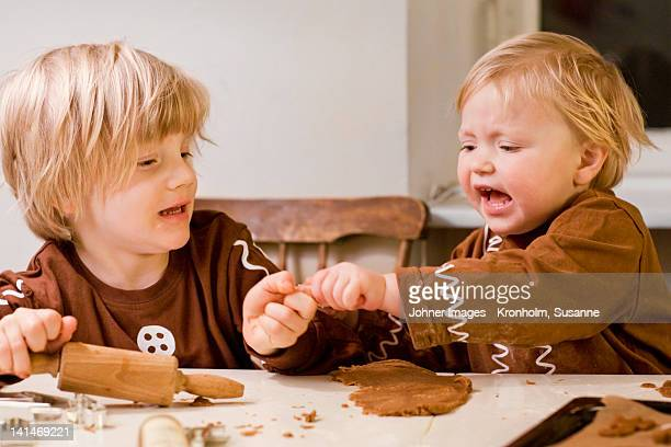 Brother and sister fighting while preparing gingerbread