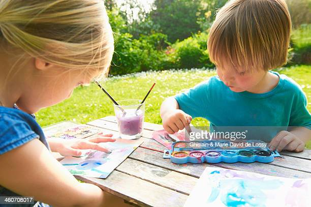 Brother and sister finger painting in garden